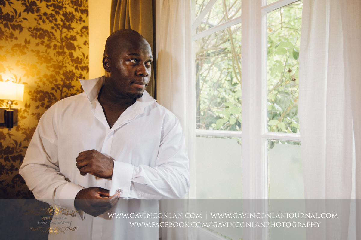 creative portrait of the groom with his shirt on fixing his cuff links at the Best Western Ivy Hill Hotel. Wedding photography at  Best Western Ivy Hill Hotel  by  gavin conlan photography Ltd