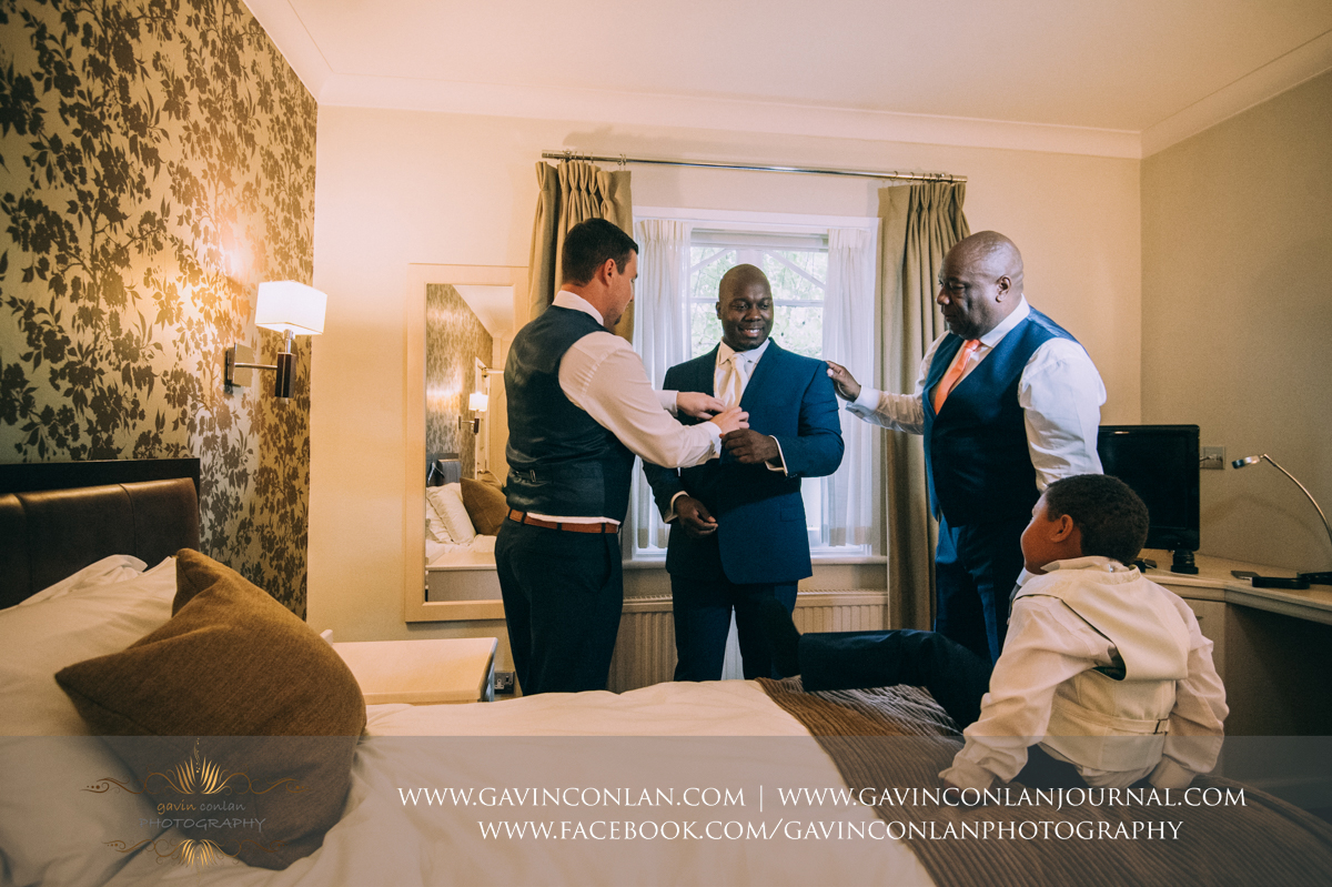 creative portrait of the best man and the grooms father helping the groom with the finishing touches of his wedding suit with his son looking up at his father at the Best Western Ivy Hill Hotel. Wedding photography at  Best Western Ivy Hill Hotel  by  gavin conlan photography Ltd