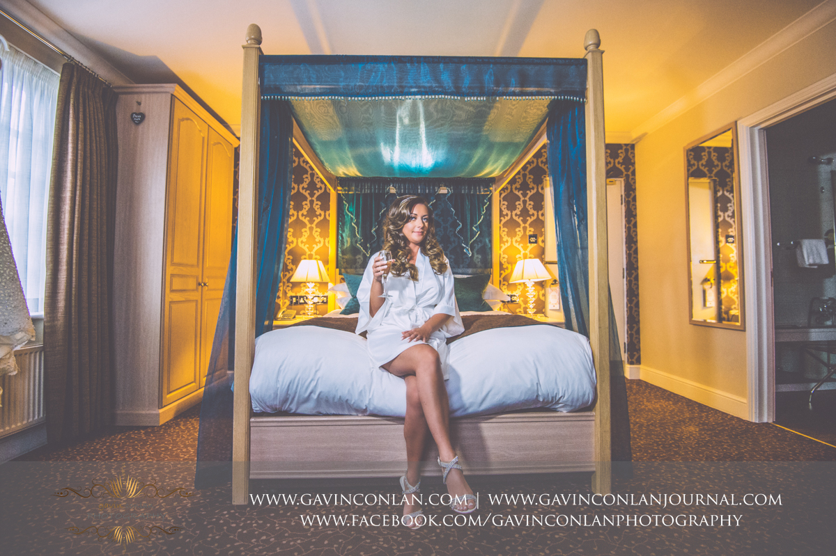 creative full length bridal portrait of the bride sitting on the bed holding a glass of champagne and showing off her beautiful wedding shoes at the Best Western Ivy Hill Hotel. Wedding photography at  Best Western Ivy Hill Hotel  by  gavin conlan photography Ltd