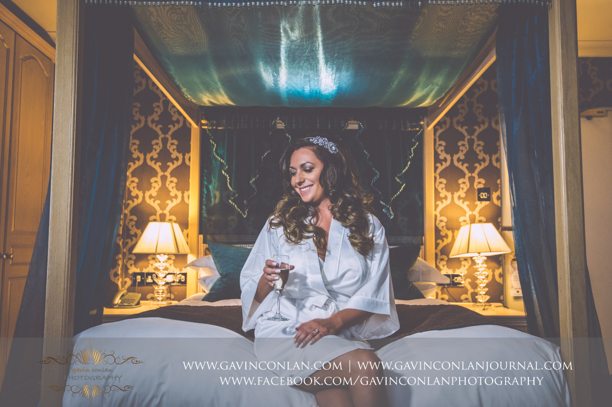 creative bridal portrait of the bride sitting on the bed holding a glass of champagne at the Best Western Ivy Hill Hotel. Wedding photography at  Best Western Ivy Hill Hotel  by  gavin conlan photography Ltd