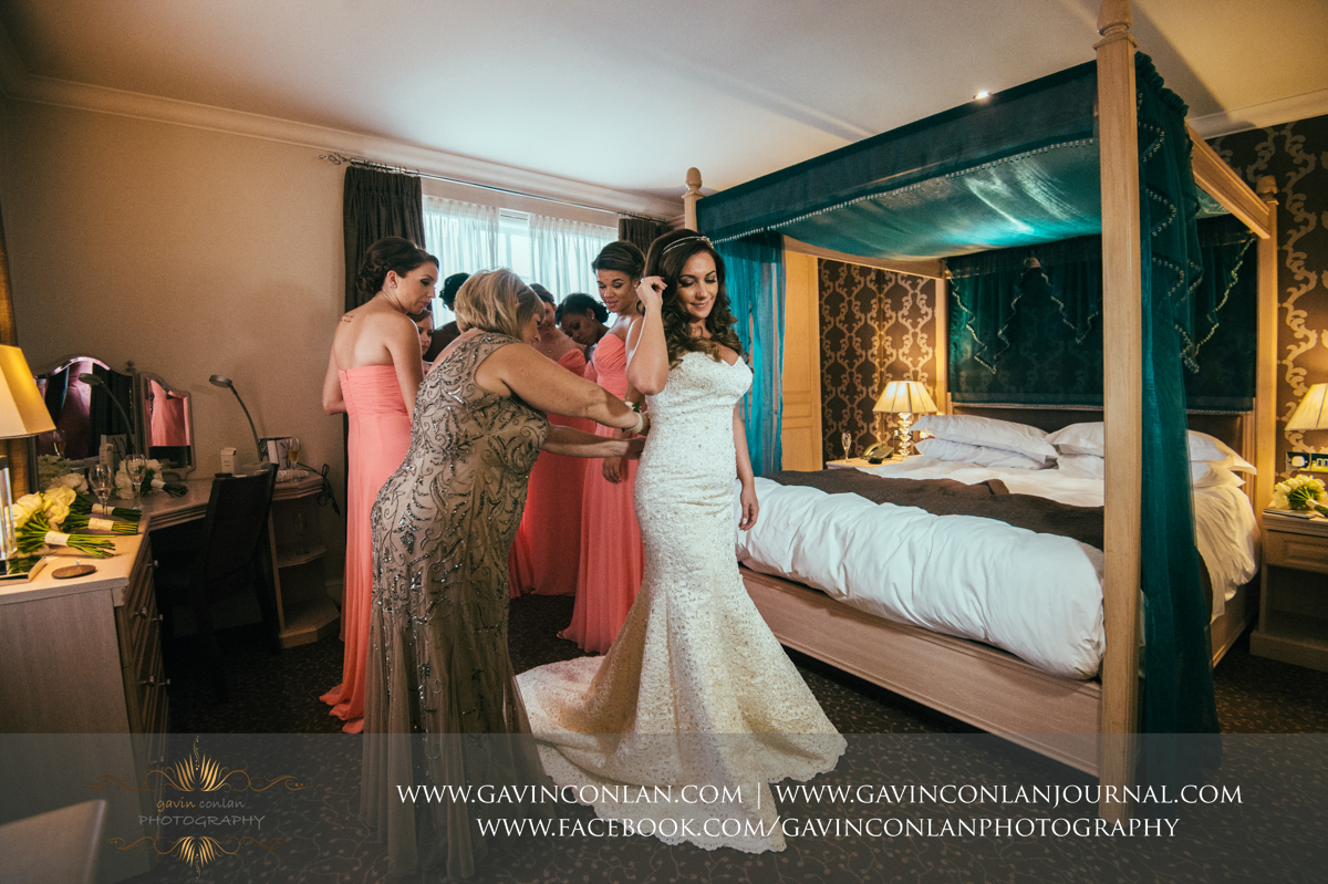 creative full length portrait showing the mother of the bride helping the bride with her dress with the bridesmaids looking on in the background at the Best Western Ivy Hill Hotel. Wedding photography at  Best Western Ivy Hill Hotel  by  gavin conlan photography Ltd