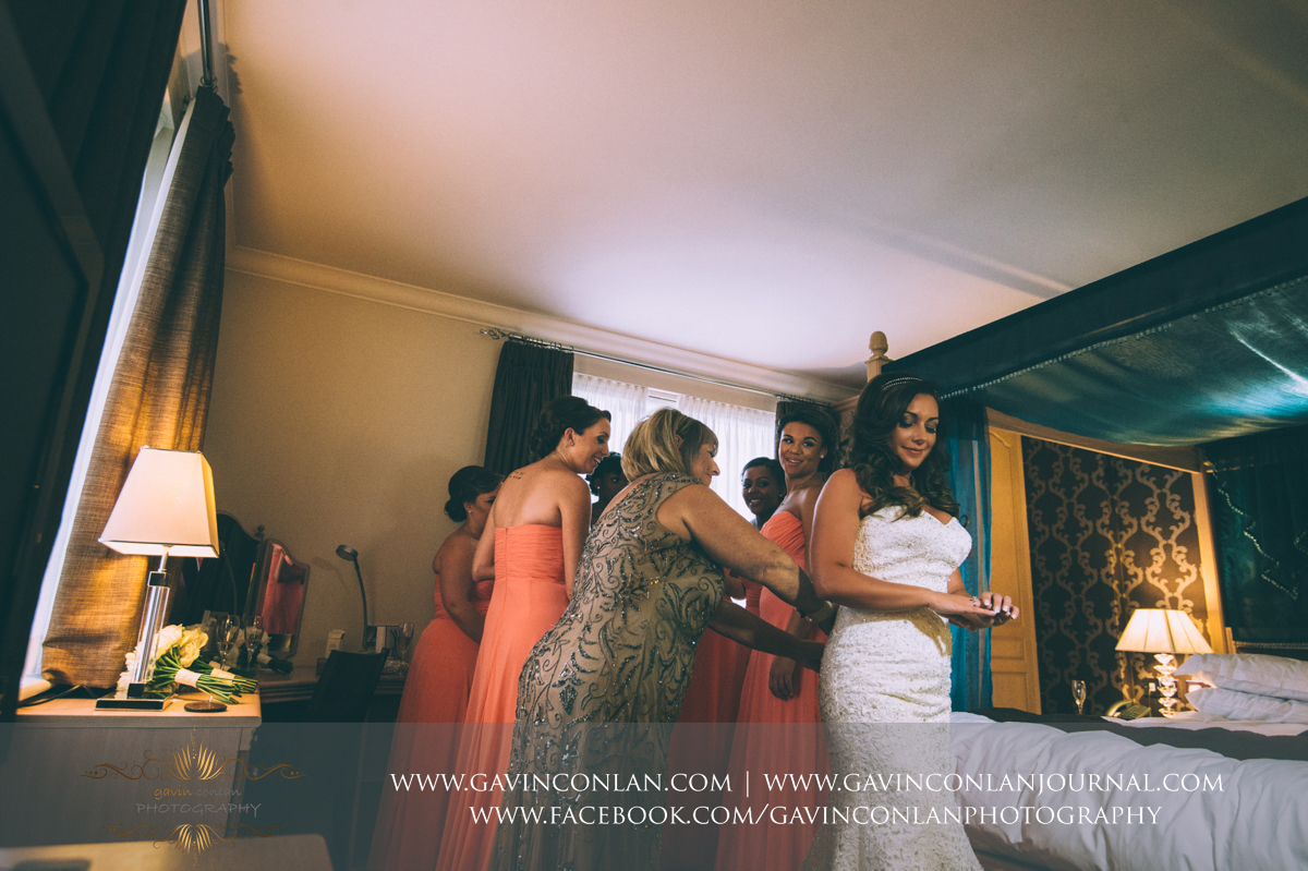 creative portrait showing the mother of the bride helping the bride with her dress with the bridesmaids looking on in the background at the Best Western Ivy Hill Hotel. Wedding photography at  Best Western Ivy Hill Hotel  by  gavin conlan photography Ltd