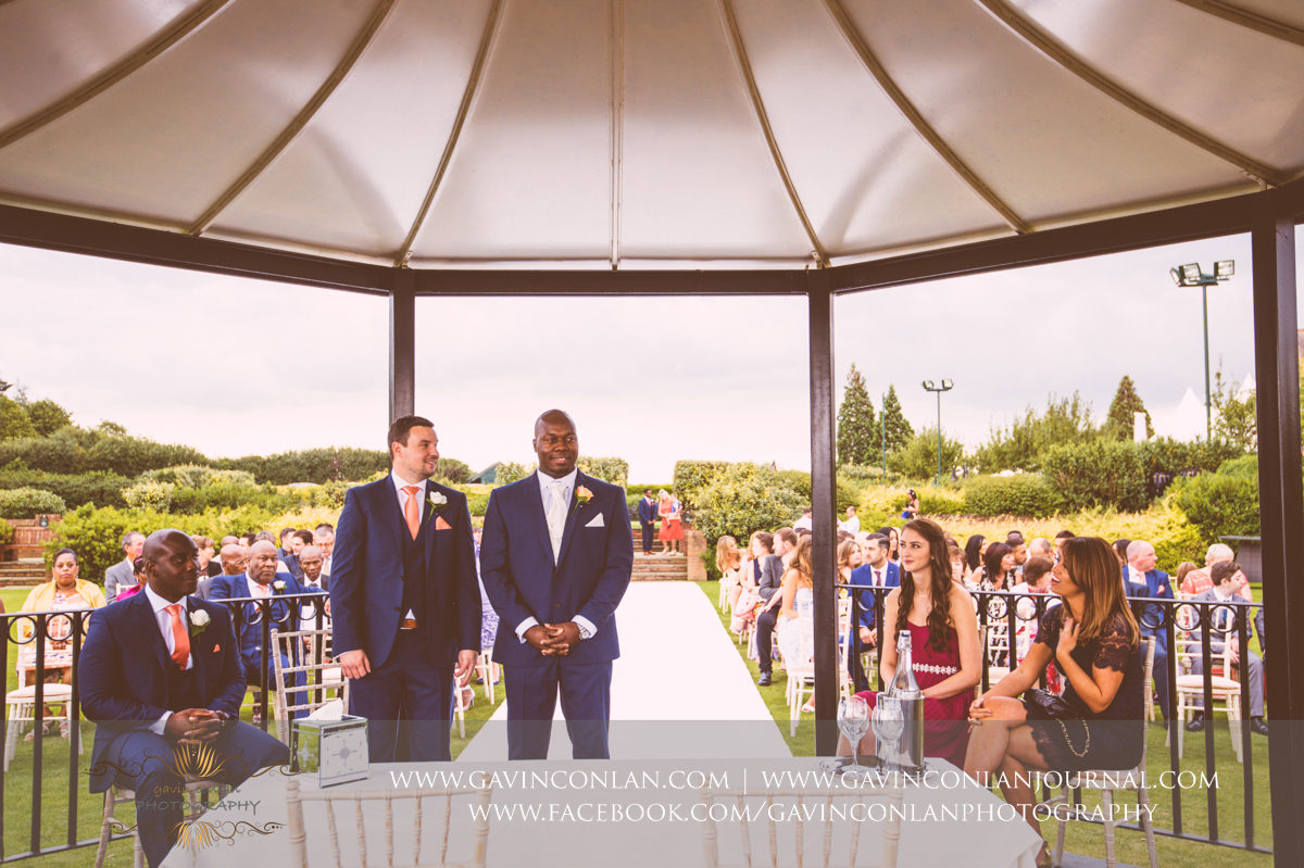 a portrait of the groom and his best man waiting on the The Lawn as the wedding ceremony begins with the bridesmaids walking down the aisle at Stock Brook Country Club. Wedding photography at  Stock Brook Country Club  by  gavin conlan photography Ltd