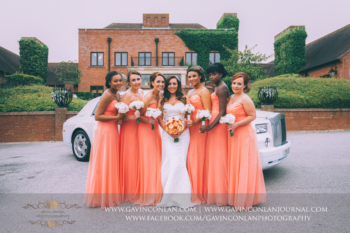 creative full length portrait of the bride and her bridesmaids with the bridal car showing the main entrance of Stock Brook Country Club. Wedding photography at  Stock Brook Country Club  by  gavin conlan photography Ltd