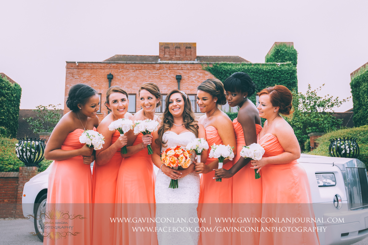 creative portrait of the bride and her bridesmaids with the bridal car showing the main entrance of Stock Brook Country Club. Wedding photography at  Stock Brook Country Club  by  gavin conlan photography Ltd