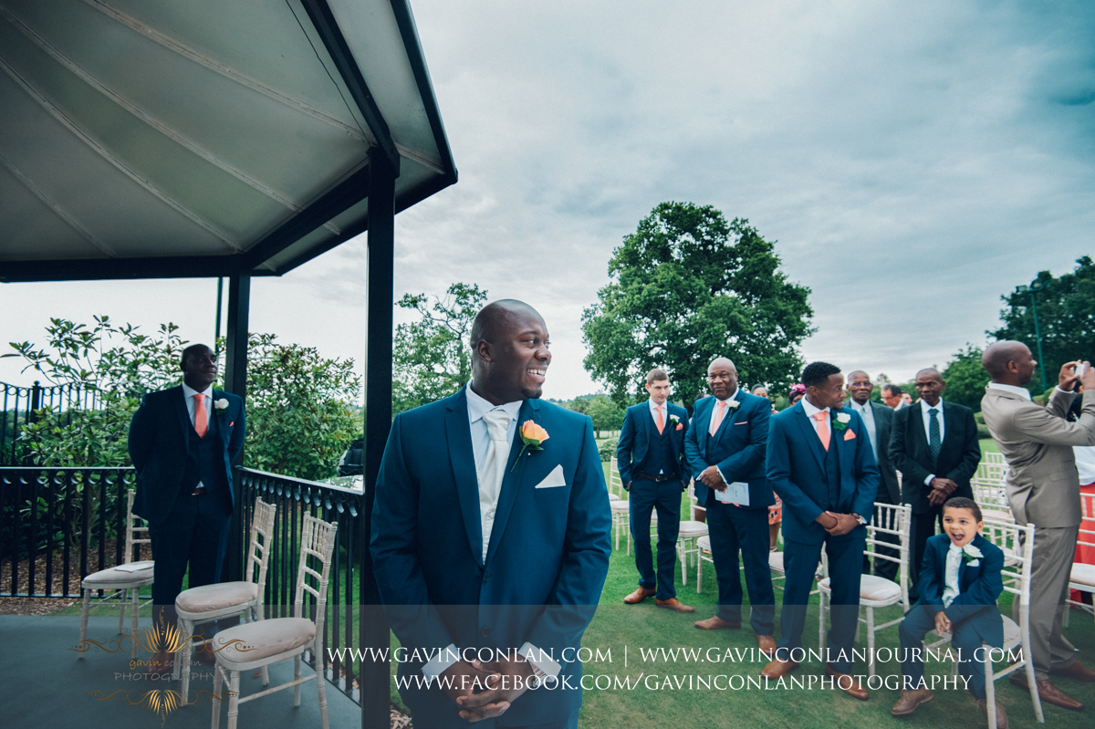 a beautiful emotive portrait of the groom looking back down the aisle seeing his bride in her wedding dress for the first time at Stock Brook Country Club. Wedding photography at  Stock Brook Country Club  by  gavin conlan photography Ltd