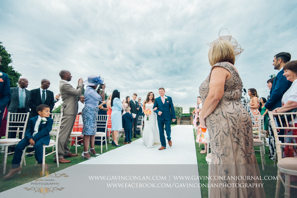 creative ceremony portrait of the bride and her father walking down the aisle with the guests looking on in celebration on The Lawn at Stock Brook Country Club. Wedding photography at  Stock Brook Country Club  by  gavin conlan photography Ltd