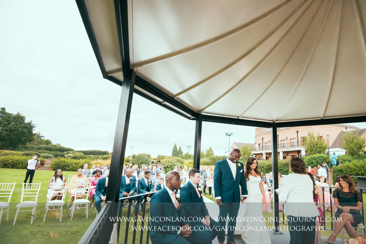 creative ceremony portrait of the bride and groom holding hands at the start of the ceremony on The Lawn at Stock Brook Country Club. Wedding photography at  Stock Brook Country Club  by  gavin conlan photography Ltd