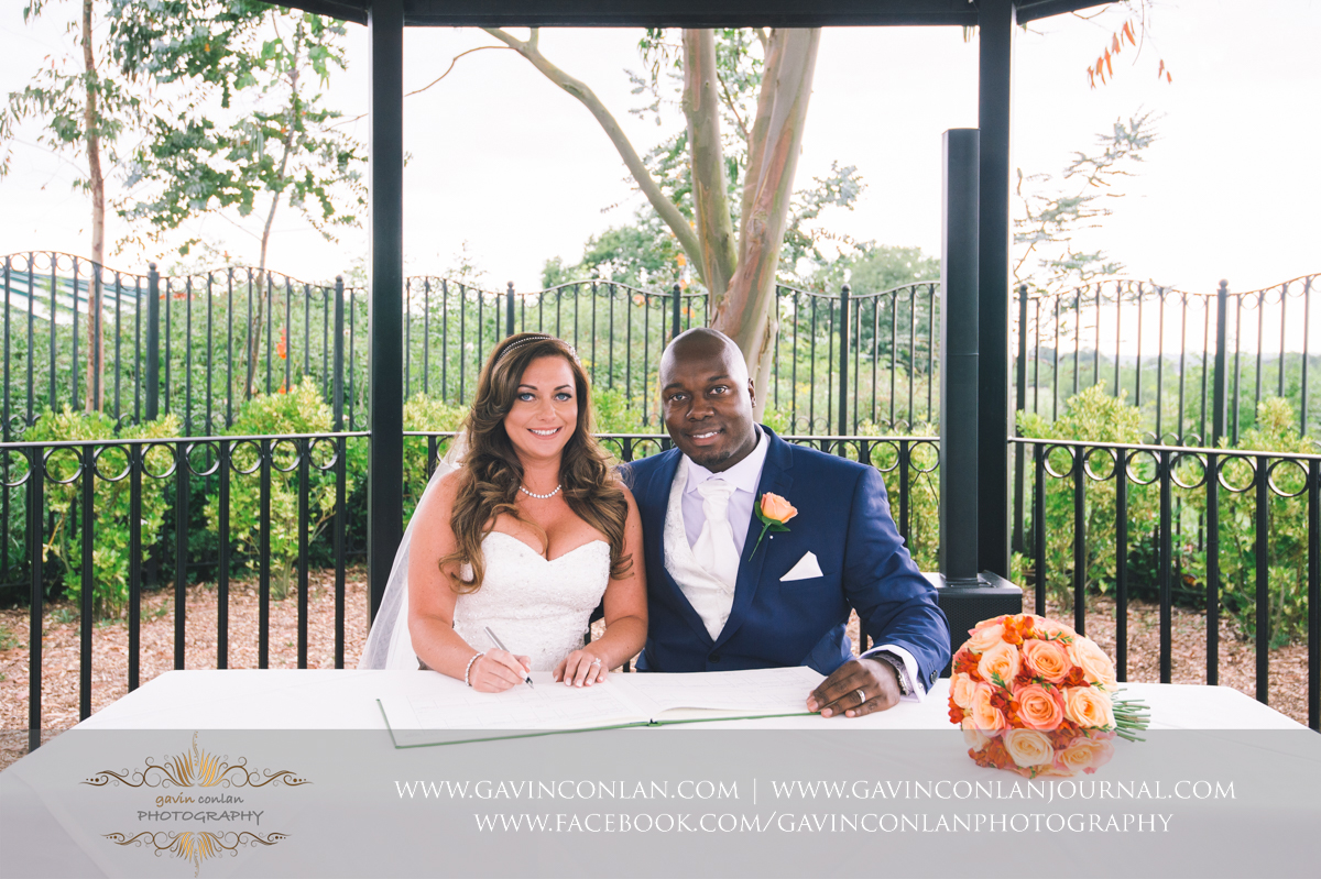 a beautiful portrait of the bride and groom signing the register on The Lawn at Stock Brook Country Club. Wedding photography at  Stock Brook Country Club  by  gavin conlan photography Ltd