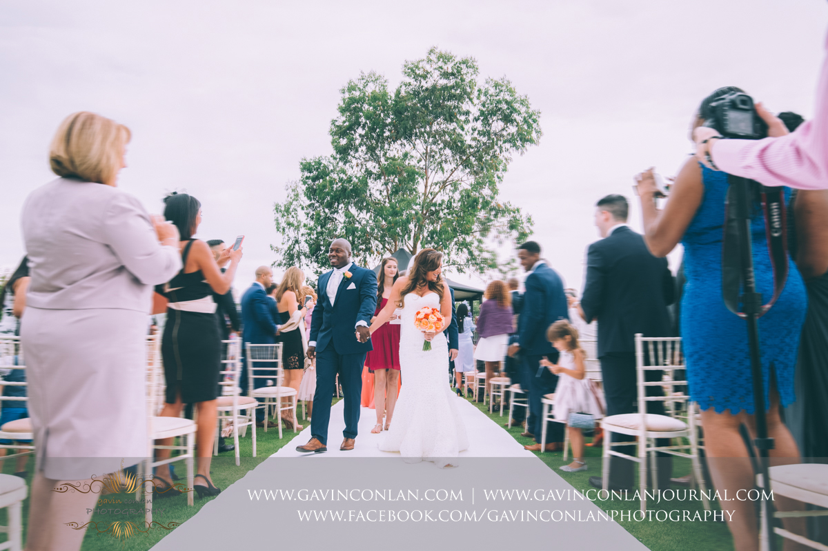 beautiful portrait full of emotion of the bride and groom walking down the aisle together as Mr and Mrs on The Lawn at Stock Brook Country Club. Wedding photography at  Stock Brook Country Club  by  gavin conlan photography Ltd