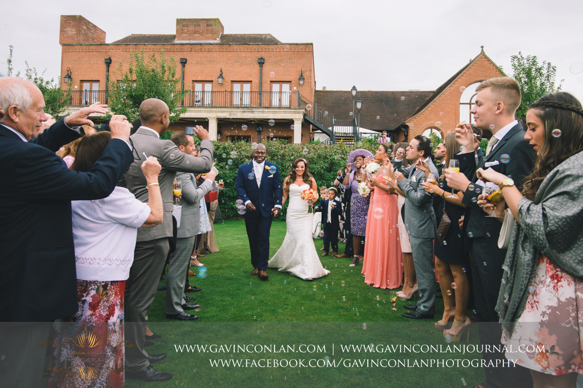 beautiful portrait of the bride and groom holding hands walking through a tunnel of bubbles set off by their family and friends on The Lawn at Stock Brook Country Club. Wedding photography at  Stock Brook Country Club  by  gavin conlan photography Ltd