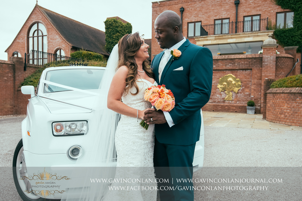 beautiful portrait of the bride and groom standing in front of their wedding car outside the main entrance to Stock Brook Country Club. Wedding photography at  Stock Brook Country Club  by  gavin conlan photography Ltd