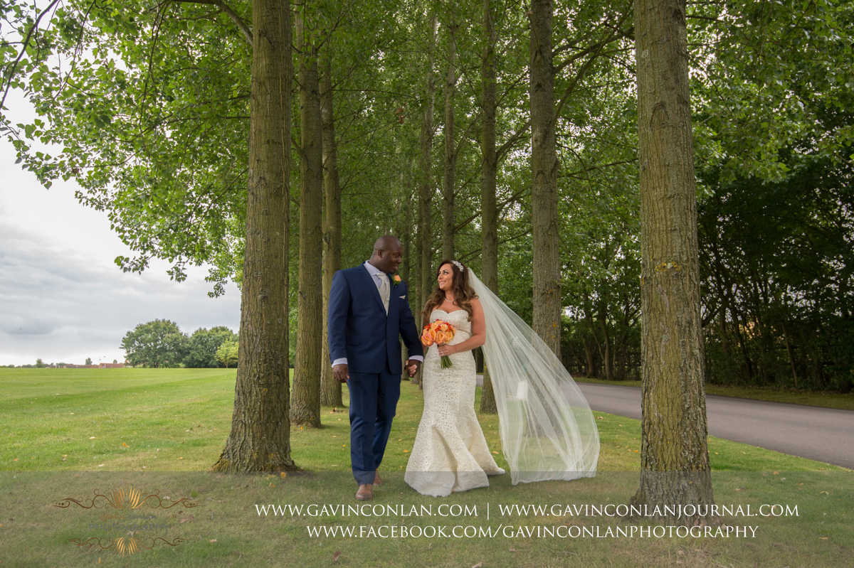 beautiful portrait of the bride and groom walking through a tunnel of trees at Stock Brook Country Club. Wedding photography at  Stock Brook Country Club  by  gavin conlan photography Ltd