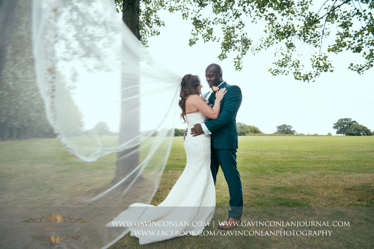 creative portrait of the bride and groom cuddling each other with the brides veil blowing in the wind at Stock Brook Country Club. Wedding photography at  Stock Brook Country Club  by  gavin conlan photography Ltd