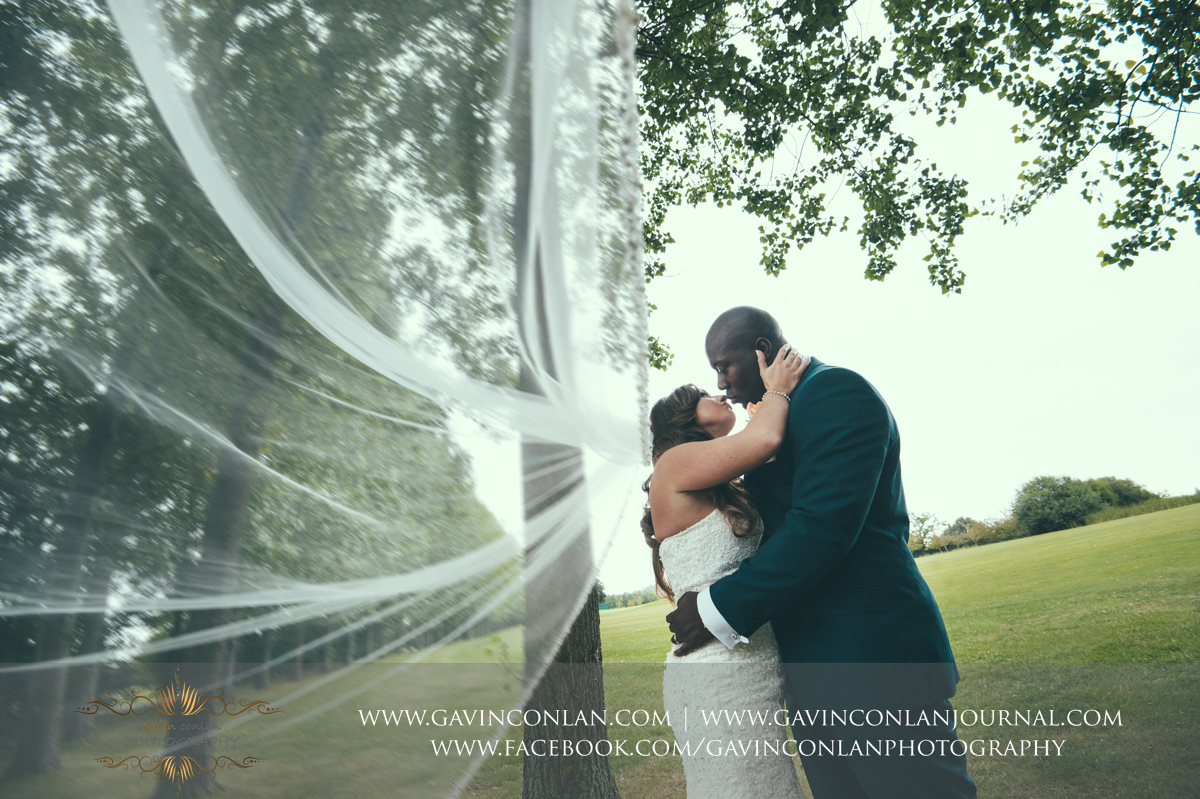 creative portrait of the bride and groom about to share a kiss with the brides veil blowing in the wind at Stock Brook Country Club. Wedding photography at  Stock Brook Country Club  by  gavin conlan photography Ltd