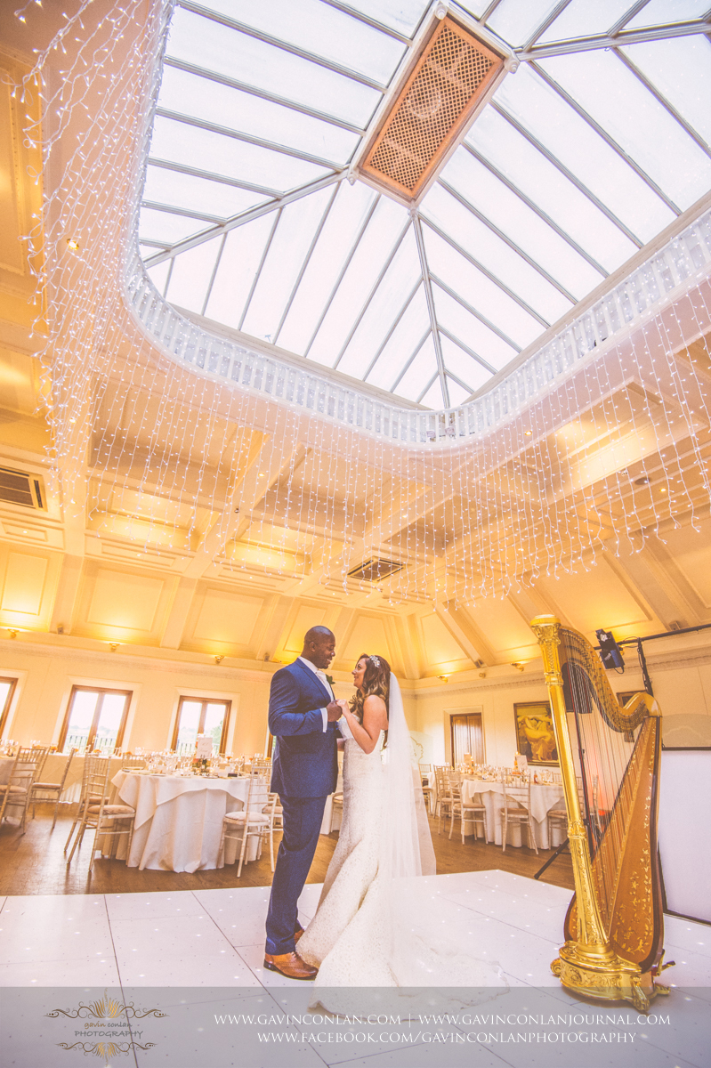 beautiful portrait of the bride and groom holding hands together in the middle of The Banqueting Suite at Stock Brook Country Club. Wedding photography at  Stock Brook Country Club  by  gavin conlan photography Ltd