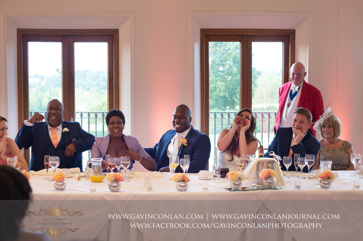amazing expressions from the top table during the best mans wedding speech in The Banqueting Suite at Stock Brook Country Club. Wedding photography at  Stock Brook Country Club  by  gavin conlan photography Ltd