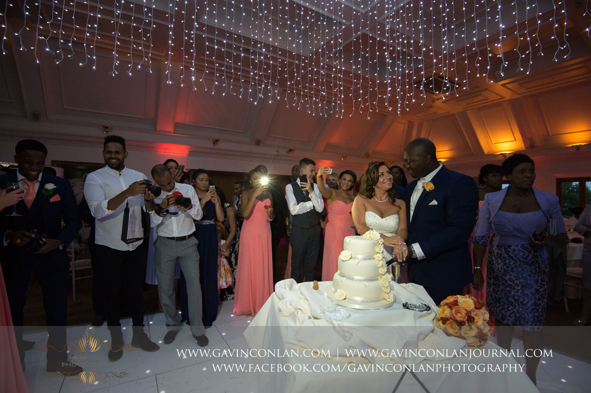 portrait of the bride and groom cutting their wedding cake with all their guests looking on in the background in The Banqueting Suite at Stock Brook Country Club. Wedding photography at  Stock Brook Country Club  by  gavin conlan photography Ltd