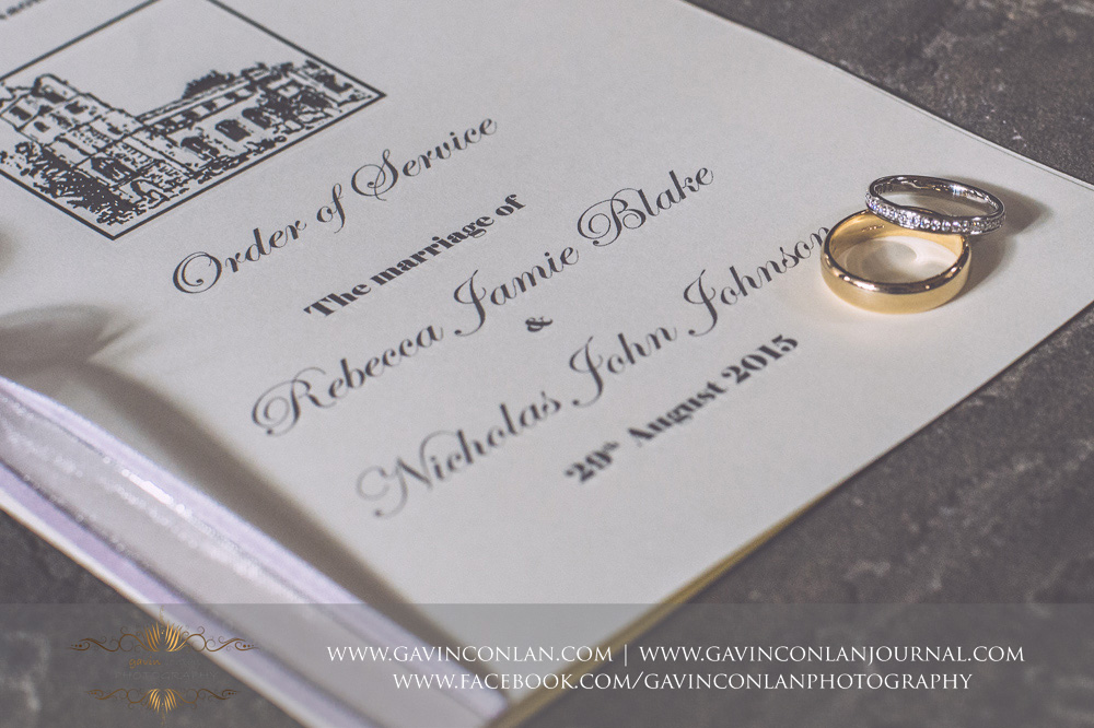 creative detail shot of their wedding rings posed on the order of service, the marriage of Rebecca Jamie Blake and Nicholas John Johnson, 29th August 2015. Essex Wedding Photography by  gavin conlan photography Ltd