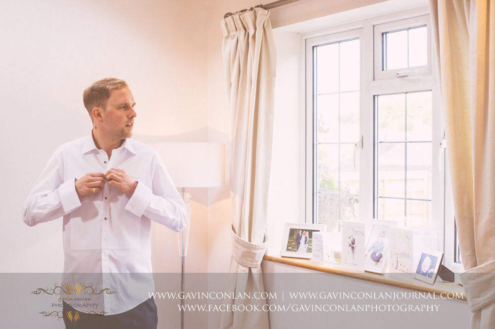 creative portrait of the groom buttoning up his shirt as he gets dressed. Essex Wedding Photography by  gavin conlan photography Ltd