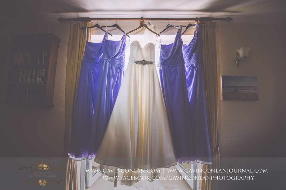 creative detail photograph showcasing the bride and bridesmaids wedding dresses hanging up together. Essex Wedding Photography by  gavin conlan photography Ltd