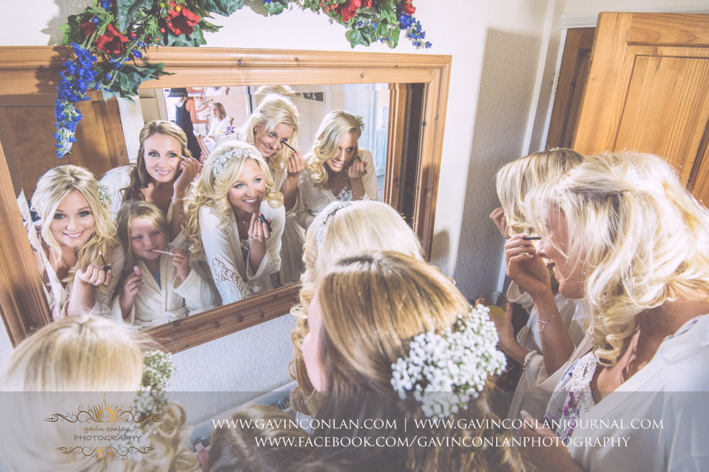brilliant portrait of the bridal party putting on their make up in the mirror. Essex Wedding Photography by  gavin conlan photography Ltd