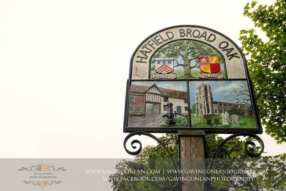 creative detail photograph of the Hatfield Broad Oak sign post showing a painting of the St Mary the Virgin Church.  Essex wedding photography at  St Mary the Virgin Church  by  gavin conlan photography Ltd