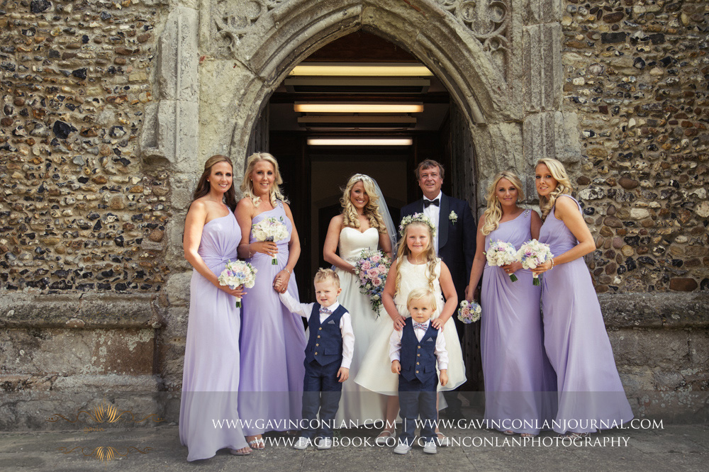 creative portrait of the bride, her bridesmaids, paige boys, flower girl and her father outside St Mary the Virgin Church.  Essex wedding photography at  St Mary the Virgin Church  by  gavin conlan photography Ltd