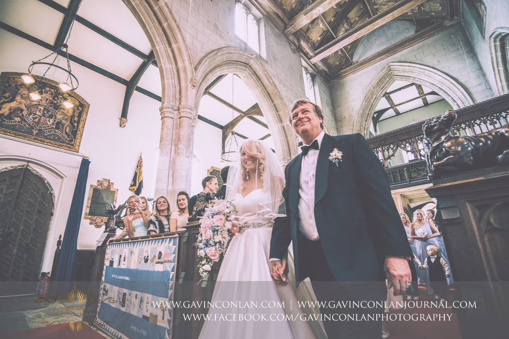 creative portrait of the bride walking down the aisle with the father at St Mary the Virgin Church.  Essex wedding photography at  St Mary the Virgin Church  by  gavin conlan photography Ltd
