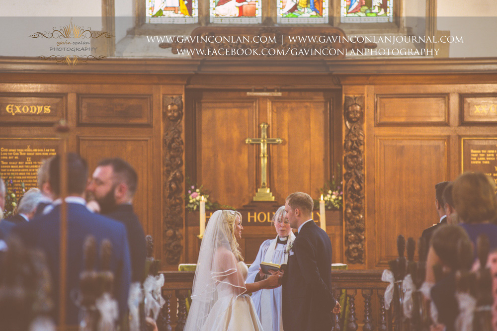 creative ceremony portrait of the bride and groom holding hands standing at the end of the aisle during the service at St Mary the Virgin Church.  Essex wedding photography at  St Mary the Virgin Church  by  gavin conlan photography Ltd