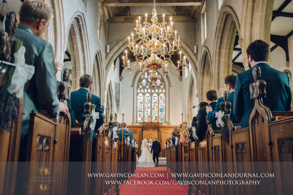 creative portrait of the bride and groom holding hands during the wedding ceremony at St Mary the Virgin Church.  Essex wedding photography at  St Mary the Virgin Church  by  gavin conlan photography Ltd