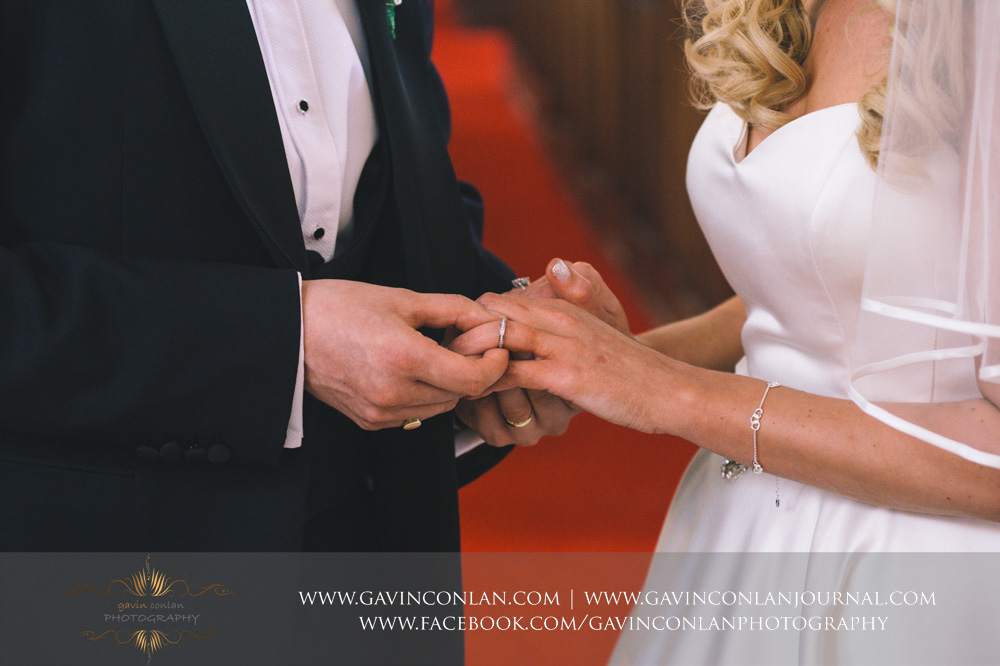 creative detail photograph of the groom putting the wedding ring on his brides finger at St Mary the Virgin Church.  Essex wedding photography at  St Mary the Virgin Church  by  gavin conlan photography Ltd