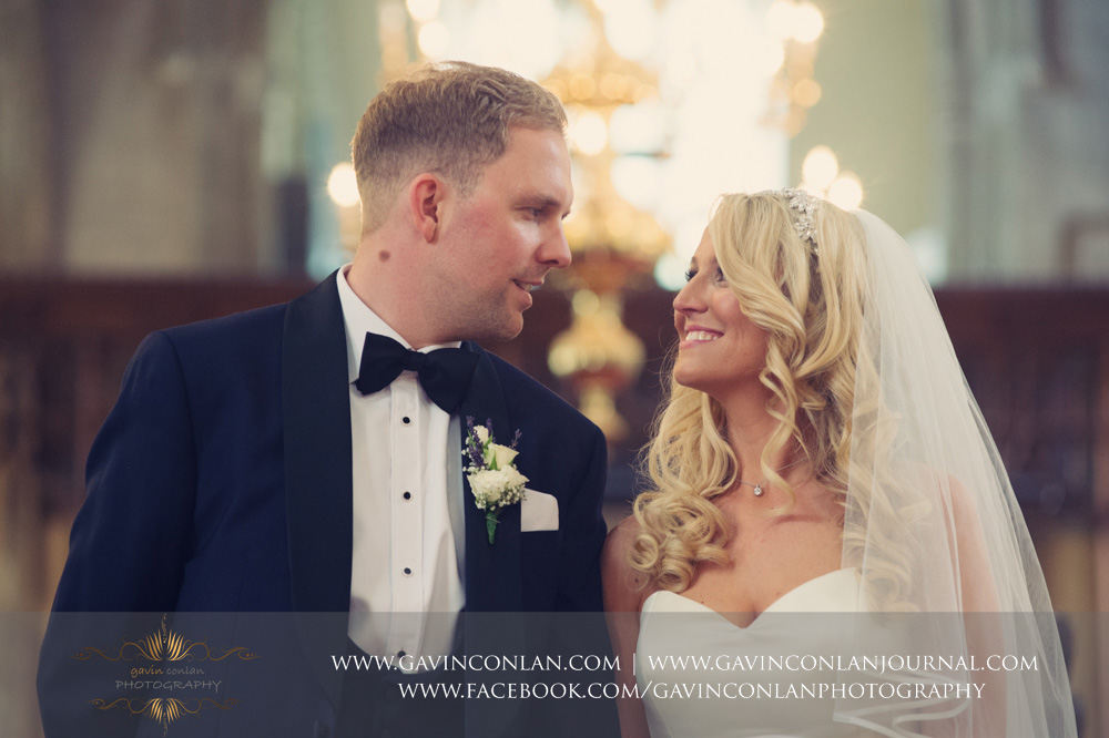 creative close portrait of the bride and groom smiling at each other during the wedding ceremony at St Mary the Virgin Church.  Essex wedding photography at  St Mary the Virgin Church  by  gavin conlan photography Ltd