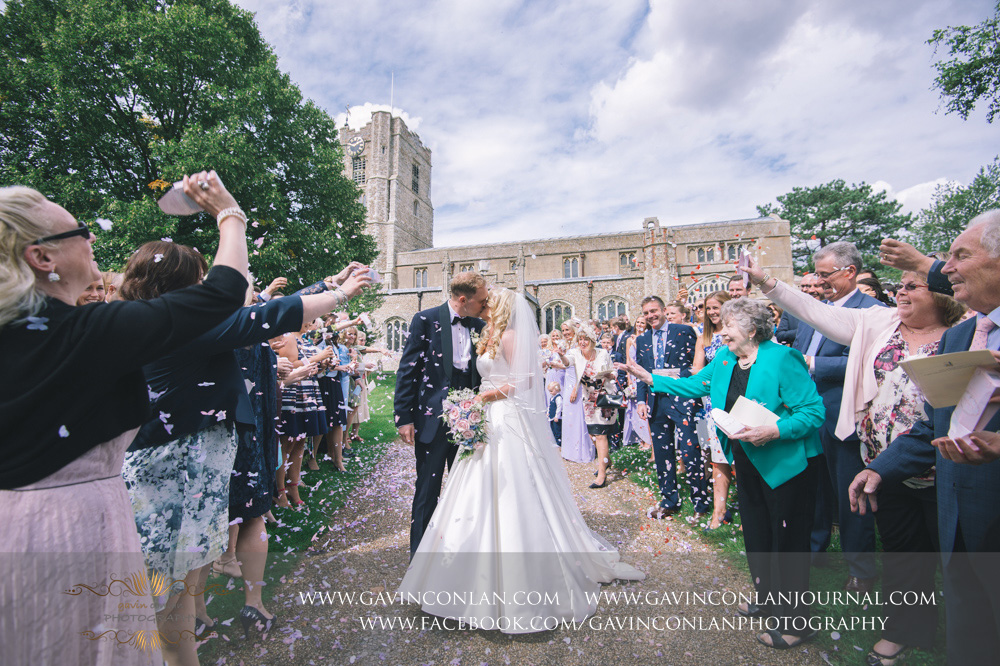 beautiful confetti photograph as the bride and groom kiss and their family and friends throw confetti over them outside St Mary the Virgin Church.  Essex wedding photography at  St Mary the Virgin Church  by  gavin conlan photography Ltd