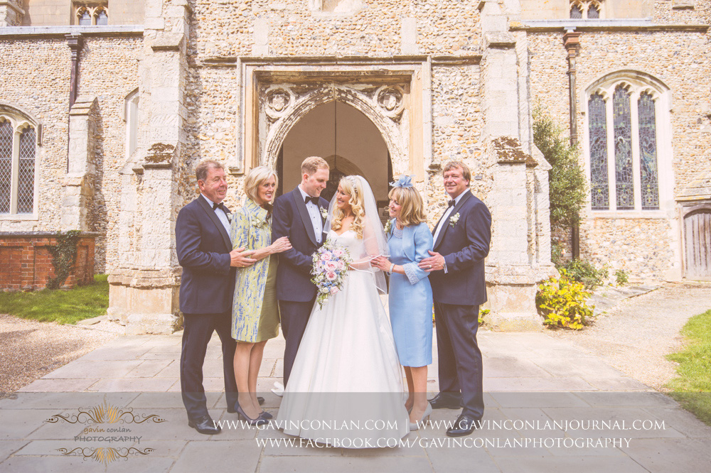 creative family portrait of the bride and groom with both their parents outside St Mary the Virgin Church.  Essex wedding photography at  St Mary the Virgin Church  by  gavin conlan photography Ltd