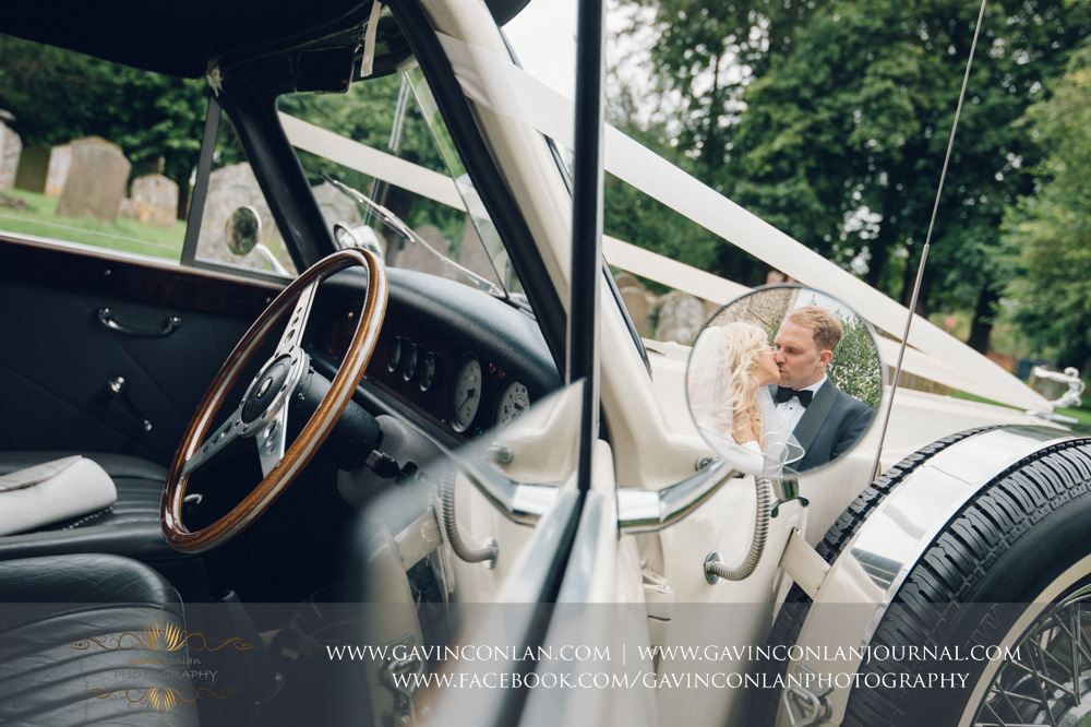 creative portrait showcasing the bride and groom kissing in the wing mirror outside St Mary the Virgin Church. Essex wedding photography at  St Mary the Virgin Church  by  gavin conlan photography Ltd