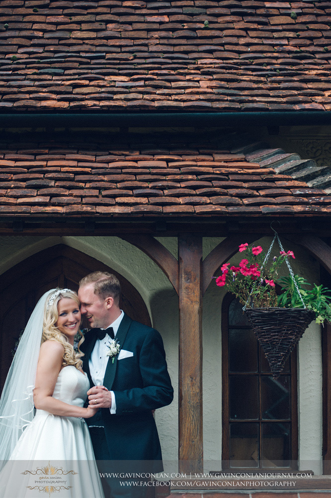 stunning portrait of the bride and groom laughing outside of Great Hallingbury Manor. Essex wedding photography at  Great Hallingbury Manor  by  gavin conlan photography Ltd