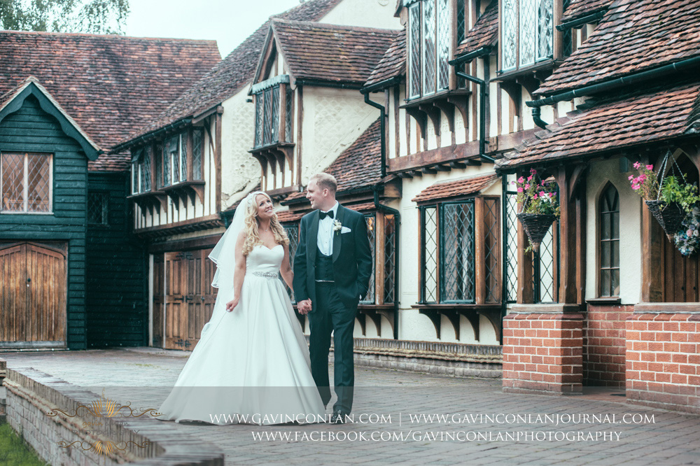a beautiful portrait of the bride and groom walking outside of Great Hallingbury Manor. Essex wedding photography at  Great Hallingbury Manor  by  gavin conlan photography Ltd
