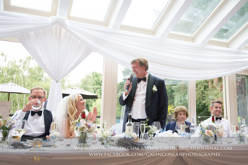 a portrait of the father of the bride laughing his speech at Great Hallingbury Manor. Essex wedding photography at  Great Hallingbury Manor  by  gavin conlan photography Ltd