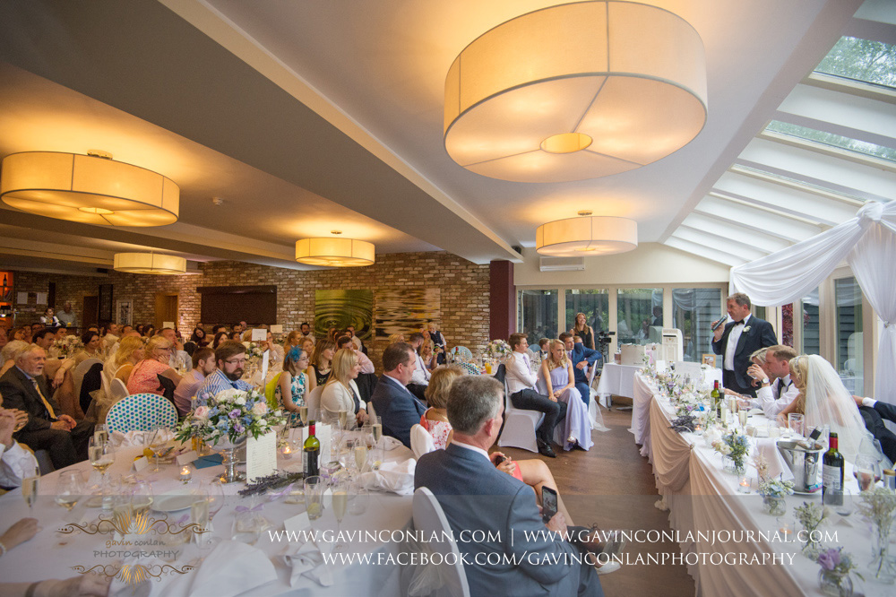 a portrait of the guests enjoying the father of the groom speech at Great Hallingbury Manor. Essex wedding photography at  Great Hallingbury Manor  by  gavin conlan photography Ltd