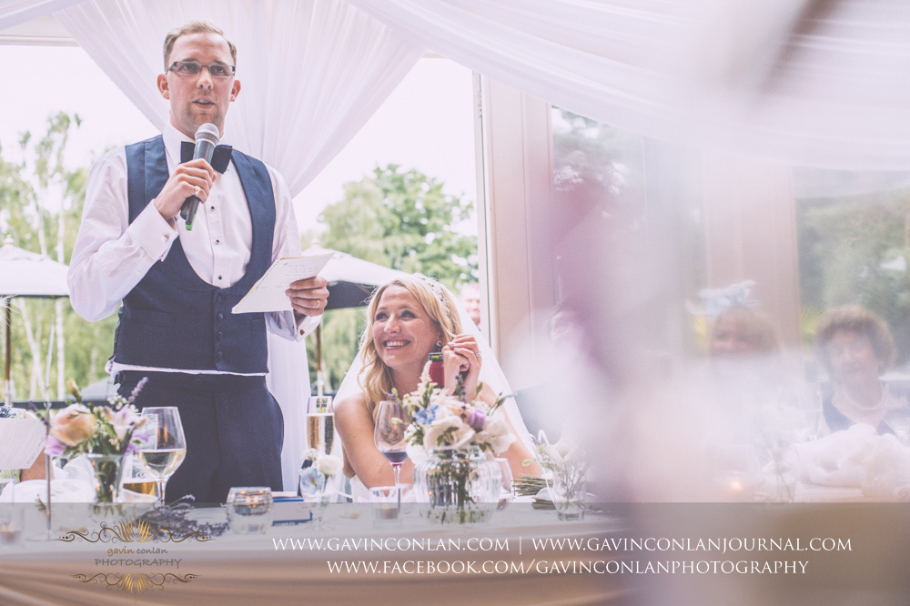 creative portrait of the groom during his speech at Great Hallingbury Manor. Essex wedding photography at  Great Hallingbury Manor  by  gavin conlan photography Ltd