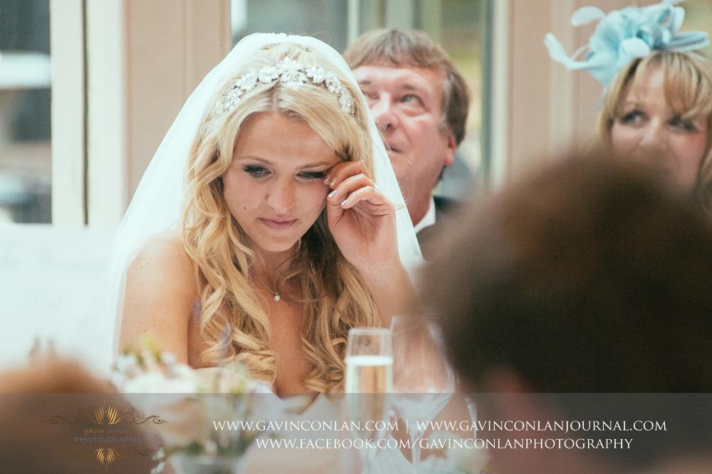 a emotional reaction from the bride during the grooms speech at Great Hallingbury Manor. Essex wedding photography at  Great Hallingbury Manor  by  gavin conlan photography Ltd