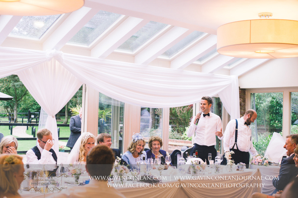 fantastic expressions of the top table during the best men speech at Great Hallingbury Manor. Essex wedding photography at  Great Hallingbury Manor  by  gavin conlan photography Ltd
