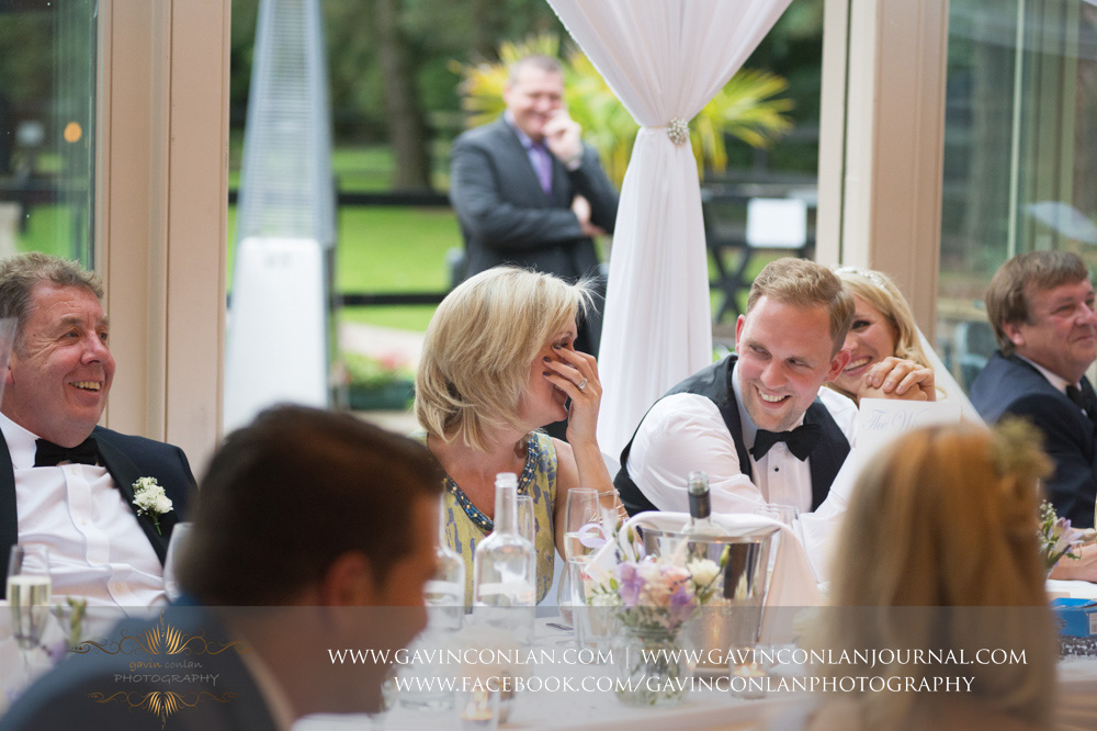 fantastic expressions of the top table during the speeches at Great Hallingbury Manor. Essex wedding photography at  Great Hallingbury Manor  by  gavin conlan photography Ltd