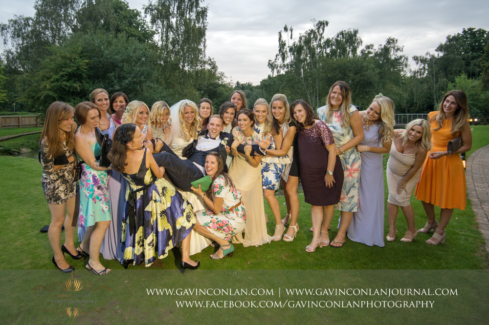 fun portrait of all the hens laughing and lifting up the groom at Great Hallingbury Manor. Essex wedding photography at  Great Hallingbury Manor  by  gavin conlan photography Ltd