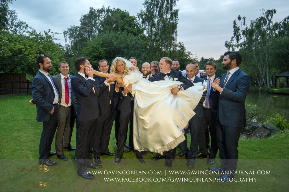 fun portrait of all the stags lifting up the bride at Great Hallingbury Manor. Essex wedding photography at  Great Hallingbury Manor  by  gavin conlan photography Ltd