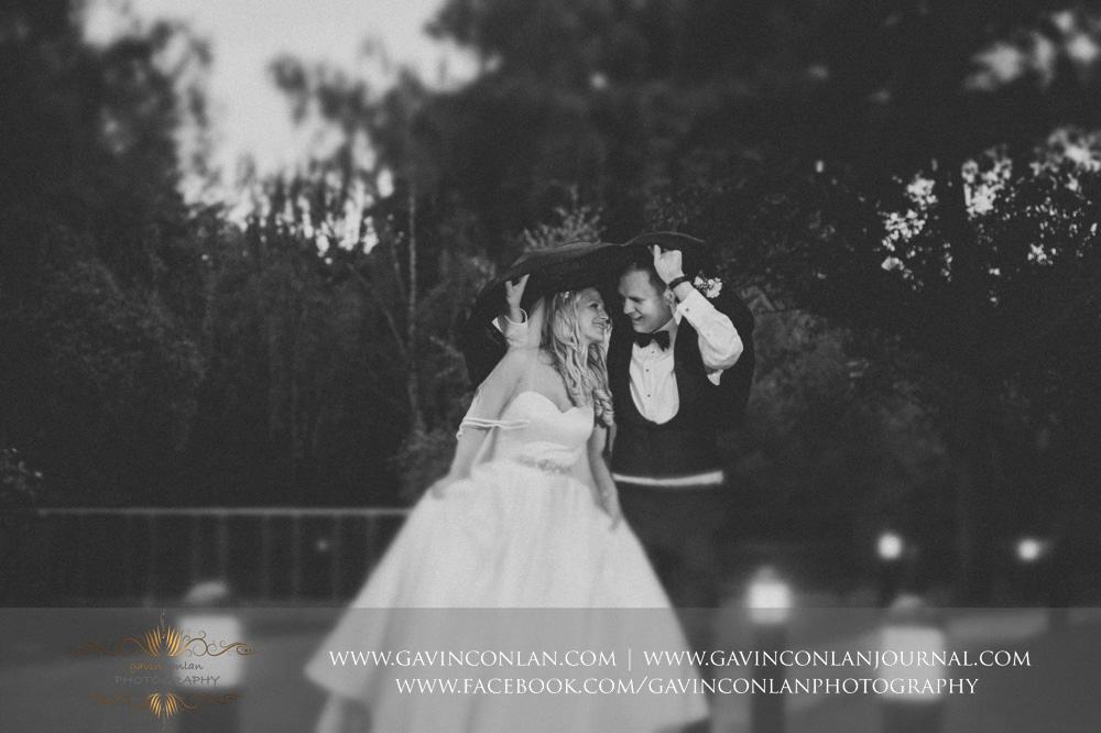 creative black and white portrait of the bride and groom taking cover under the grooms jacket in the rain at Great Hallingbury Manor. Essex wedding photography at  Great Hallingbury Manor  by  gavin conlan photography Ltd