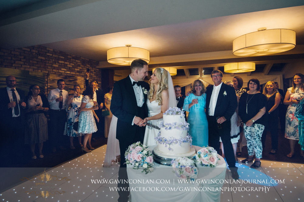 portrait of the bride and groom cutting their wedding cake on the dane floor with their friends and family in the background at Great Hallingbury Manor. Essex wedding photography at  Great Hallingbury Manor  by  gavin conlan photography Ltd