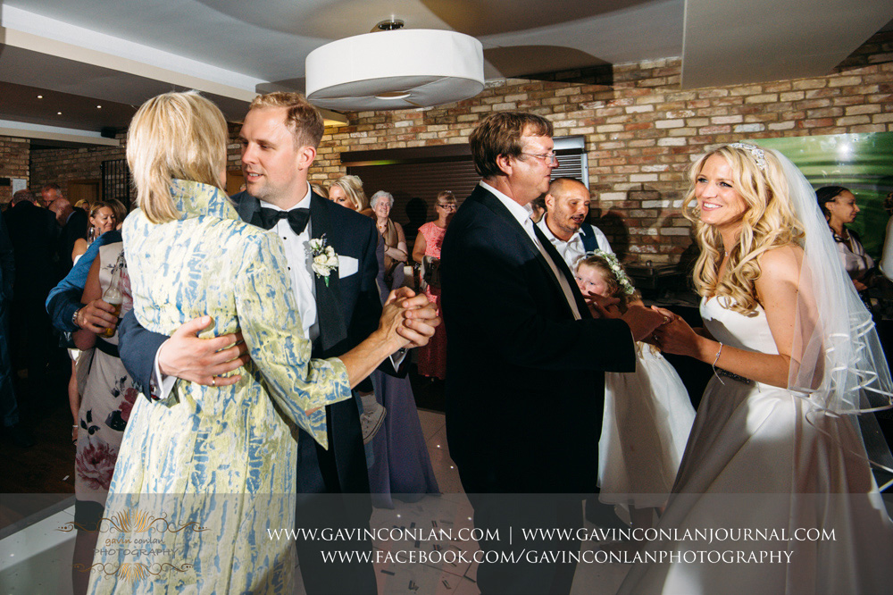 beautiful portrait of the bride dancing with her father and the groom dancing with his mother at Great Hallingbury Manor. Essex wedding photography at  Great Hallingbury Manor  by  gavin conlan photography Ltd