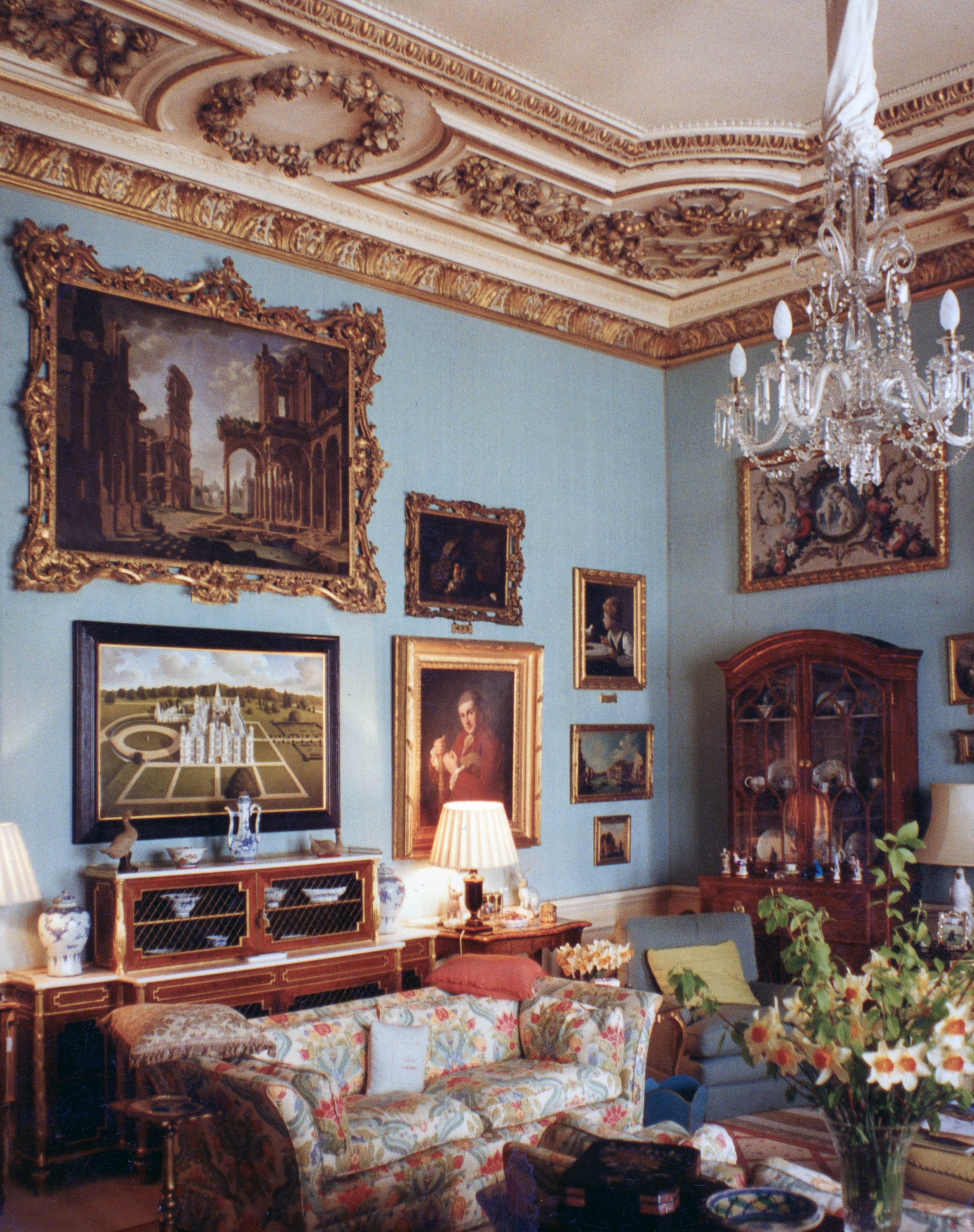 One of Jonathan Myles-Lea's paintings of Burghley hanging in the Blue Sitting Room inside the house. Above the painting hangs a capriccio by Giovanni Paolo Pannini and to the right is Angelica Kaufman's self-portrait.